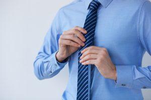 man adjusting his tie